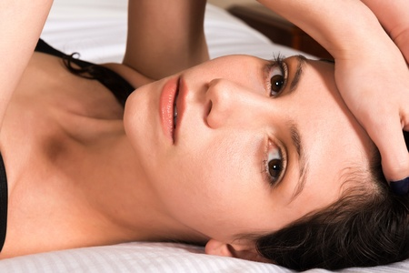 Closeup on the face of a young brunette lying in bed Stock Photo - 15920048
