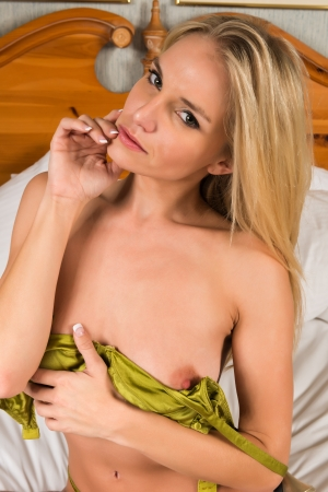 Pretty young blonde in metallic green lingerie Stock Photo