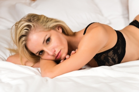 Pretty young blonde dressed in black lingerie photo