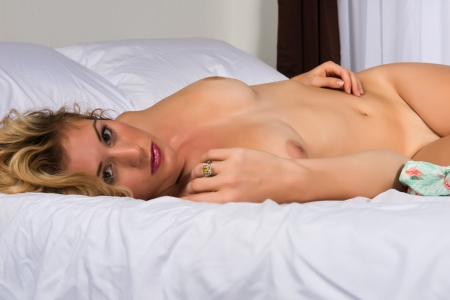 Beautiful tall blonde lying nude in bed photo