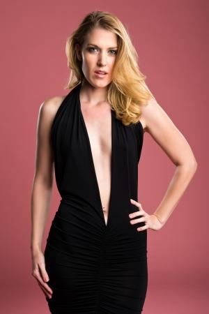 sheath: Beautiful blonde in a black sheath dress Stock Photo