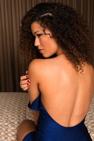 bare shoulders: Beautiful wavy haired multiracial woman dressed in blue Stock Photo