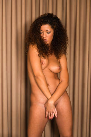 topless brunette: Beautiful wavy haired multiracial woman nude in front of a curtain Stock Photo