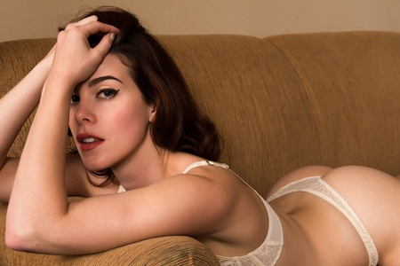 couches: Pretty young redhead dressed in white lingerie Stock Photo