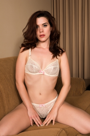Pretty young redhead dressed in white lingerie Stock Photo