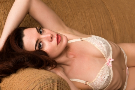 red sofa: Pretty young redhead dressed in white lingerie Stock Photo