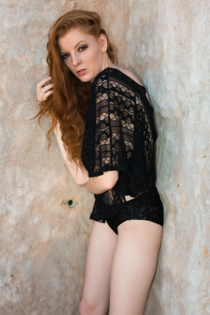 Tall young redhead dressed in black lingerie photo