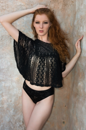 Tall young redhead dressed in black lingerie