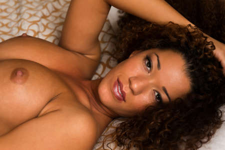 Beautiful wavy haired multiracial woman nude in bed