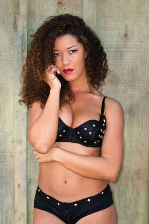 Beautiful wavy haired multiracial woman in a black bra and shorts photo