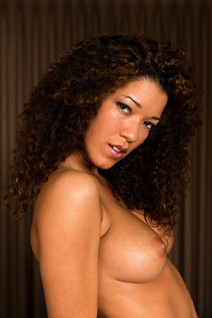 Beautiful wavy haired multiracial woman nude in bed Stock Photo - 16639203