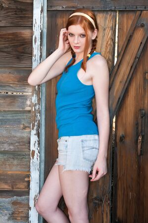 Tall young redhead in a blue top and denim shorts photo