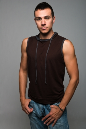 bluejeans: Handsome young man in a sleeveless hoodie