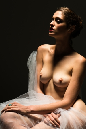 Tall nude brunette in deep shadow