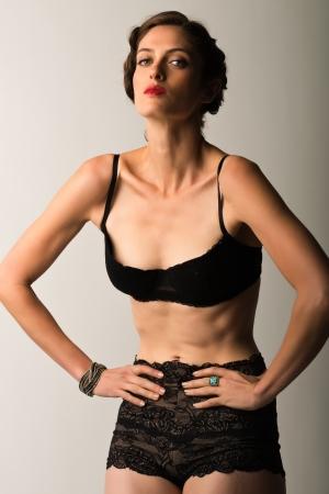 Tall slender brunette in vintage black lingerie 免版税图像