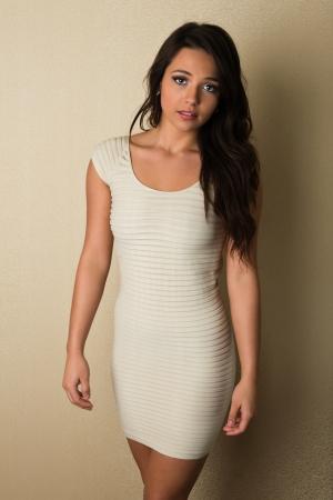 Pretty petite brunette in a skintight white dress Stock Photo