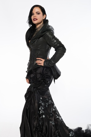 Pretty slender brunette in a long black gown and leather jacket