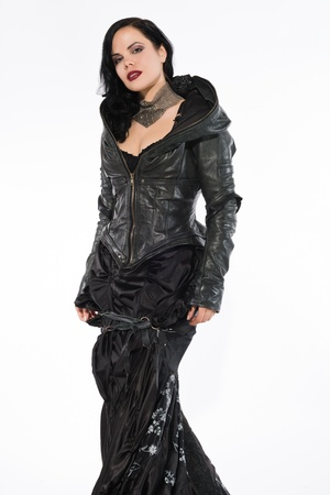 Pretty slender brunette in a long black gown and leather jacket photo