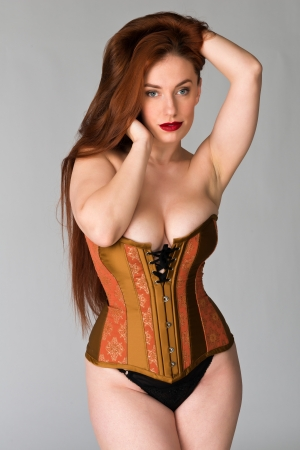 Pretty young redhead in a copper and brass corset
