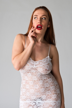 Pretty young redhead in a sheer white slip photo