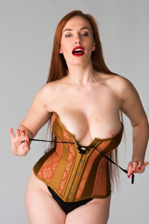 Pretty young redhead in a copper and brass corset photo