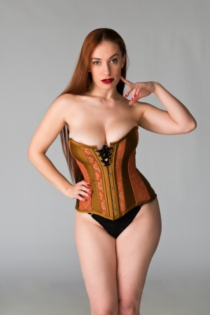 curvy: Pretty young redhead in a copper and brass corset