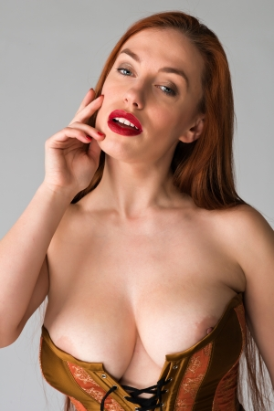 undergarments: Pretty young redhead in a copper and brass corset