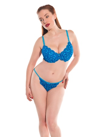 redhead lingerie: Pretty young redhead dressed in turquoise lingerie Stock Photo