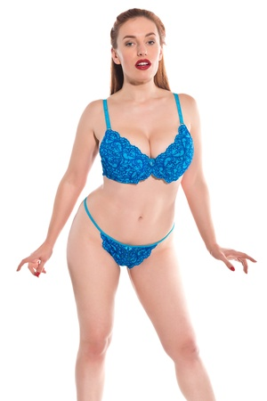 Pretty young redhead dressed in turquoise lingerie photo