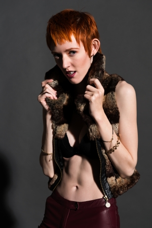 Pretty slender redhead in a fake fur jacket photo