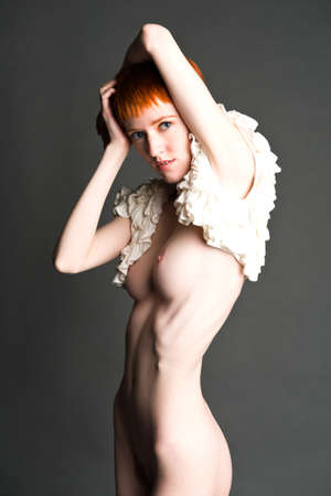 Pretty slender nude redhead in a frilly white blouse Stock Photo
