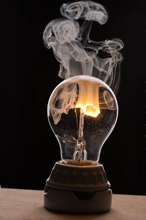 Smoke rising from a broken light bulb Imagens