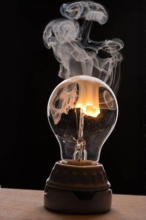 Smoke rising from a broken light bulb Banco de Imagens
