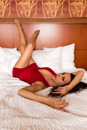 girl lying: Pretty young brunette in a tight red dress Stock Photo