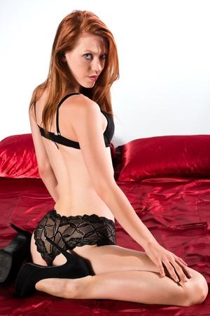 ropa interior femenina: Hermosa pelirroja alta en la cama en ropa interior negro