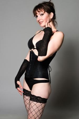fishnet stockings: Tall pretty brunette dressed in black lingerie Stock Photo