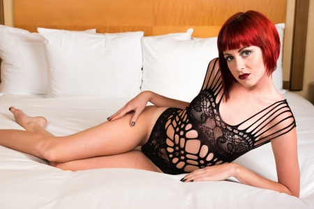 petite: Pretty petite redhead lying in bed in a black bodysuit Stock Photo