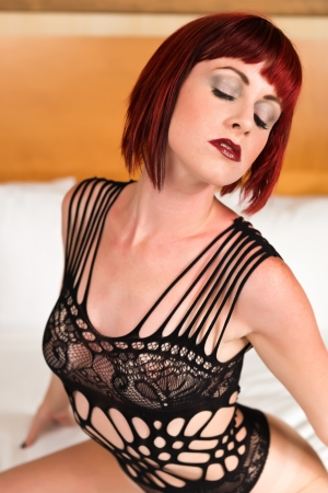 Pretty petite redhead sitting in bed in a black bodysuit Stock Photo - 20943280