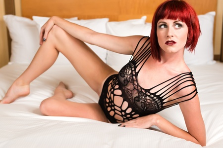 Pretty petite redhead lying in bed in a black bodysuit Stock Photo - 20943283