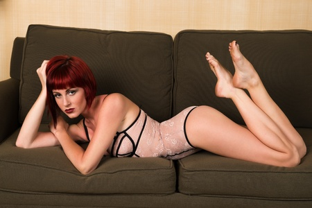 Pretty petite redhead lying on a green couch photo