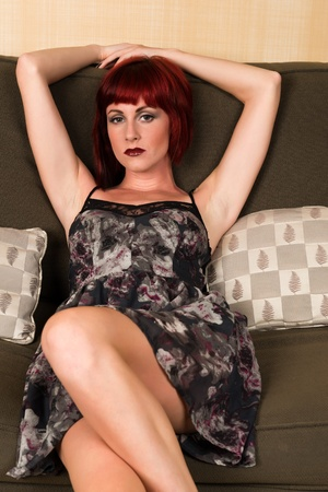 Pretty petite redhead sitting on a green couch photo