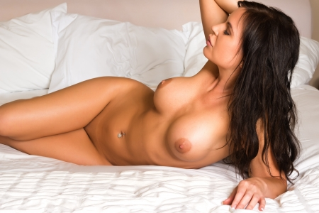 Beautiful shapely brunette lying nude in bed