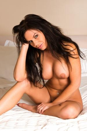 jeunes filles nues: Belle brune assise galb�es nu dans le lit Banque d'images