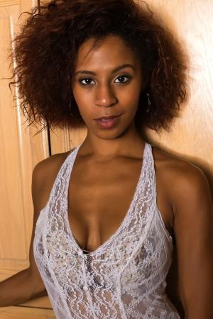 Pretty petite black woman in a white lace blouse