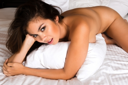 Beautiful young Eurasian woman lying in bed