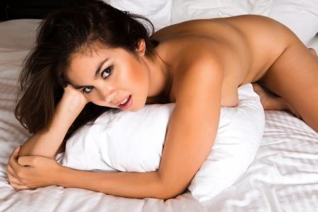 Beautiful young Eurasian woman lying in bed