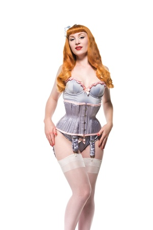 Beautiful young redhead dressed in vintage lingerie