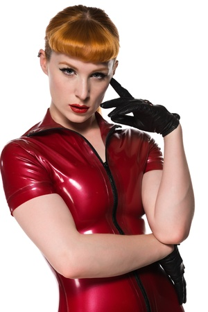 rubber: Beautiful young redhead in a red latex dress Stock Photo
