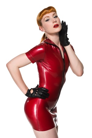 short gloves: Beautiful young redhead in a red latex dress Stock Photo
