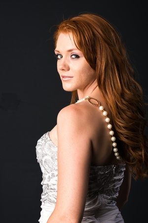 Pretty young freckled redhead in a strapless gray dress Stock Photo